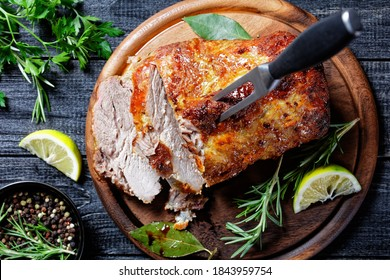 Sunday roasted pork tenderloin, juicy and succulent oven-baked piece of meat rubbed with mustard and spices: rosemary, bay leaf, lime juice, and pepper on a wooden background, close-up, top view