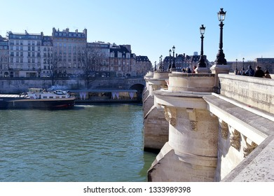 Sunday winter morning strollers cross the Pont Neuf, the oldest  bridge in Paris, from Ile de la Cite to the Left Bank of the Seine with the mascarons, the stone masks, on the pillars clearly visible.