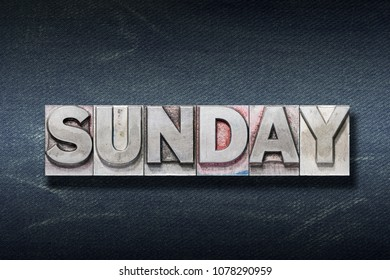 Sunday word made from metallic letterpress on dark jeans background