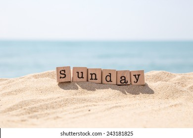 Sunday word on wood rubber stamps stack on beach with beautiful blue sea view on background, day and time concepts