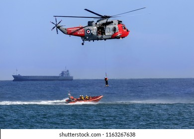 Sunderland. England. 07.25.15. Royal Navy Sea King Search and Rescue helicopter lifting a casualty from a small boat in a busy shipping lane off the northeast coast of the United Kingdom.