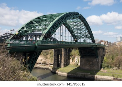 Sunderland - Great Britain / April 13, 2019 : Old historic Victorian metal arched road bridge crossing spanning a river with blue sky