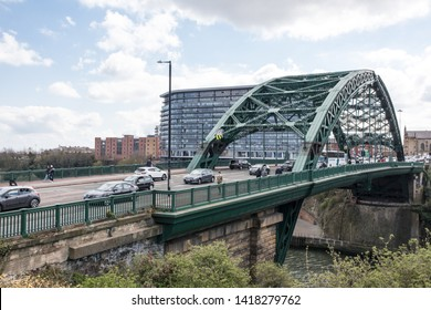 Sunderland - Great Britain / April 13, 2019 : Arch bridge with car traffic crossing river.  Metal arch Victorian construction