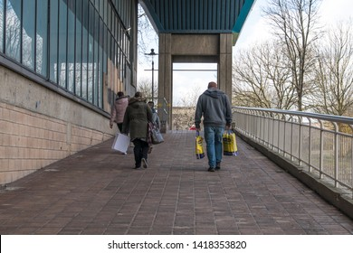 Sunderland - Great Britain / April 13, 2019 : People walking away up a ramp carrying shopping bags.