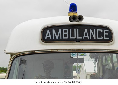 Sunderland, UK - 28th July 2019: FORD classic and vintage car show at the Sunderland air show. Traditional historic ford ambulance with blue siren and Skelton in the drivers seat