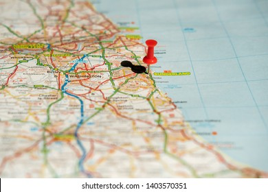 Sunderland, UK - Circa May 2019: Shallow focus of a red push-pin seen located at the centre of a northern British city on the east coast. A large part of the road network can also be seen on the map.