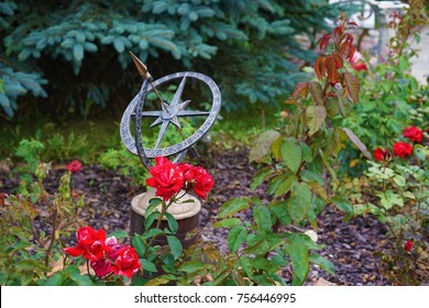 Sundial in the garden surrounded by red roses
