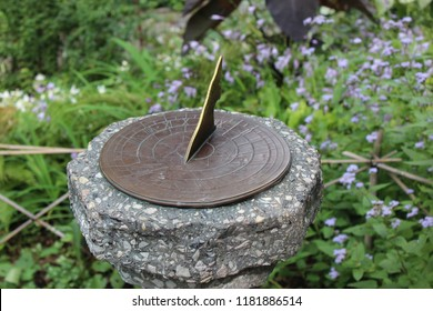 Sundial In A Lush Garden With Flowers
