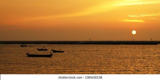 Sundown and fisherman boat on the Angsila Bay in Bangsan Beach, Thailand