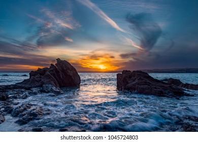 Sundown Framed Between Two Rocks at Polkerris in Cornwall