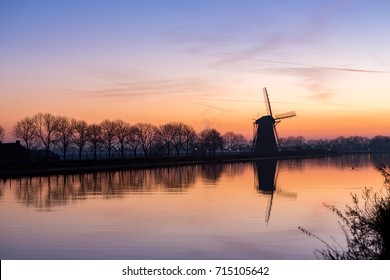 "Sundown at the historic windmill ""the Googermolen"" from 1717 with reflection in the water on the Ringvaart canal in Nieuwe Wetering the Netherlands."