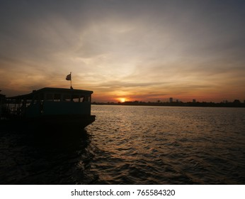 The sundown to the river and the ferry boat of Thai's style.