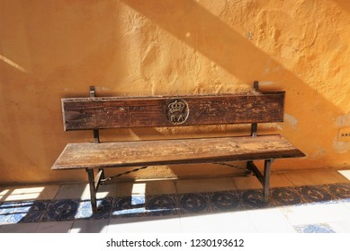 A sun-drenched old wooden Bench against an ochre Wall in one of the Courtyards of the Real Alcázar, Seville, Spain