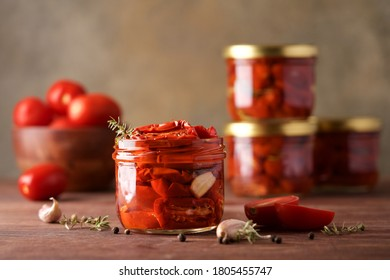 Sun-dried tomatoes in jar with spices and herbs. Autumn seasonal pickled or fermented colorful vegetables. Fall home food preserving or canning