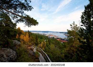 Sundsvall, Sweden - Jul 29, 2021: The hiking trail up to the northern mountain with view towards east water entrance to Sundsvall with the Sundsvall bridge and heavy industries in background.