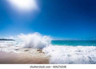 A sun-filled Caribbean beach scene with a stop-action splashing wave