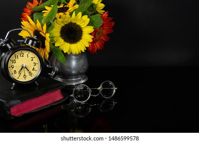 sunflower bouquet in pewter jug with Bible and old eyeglasses on black reflection