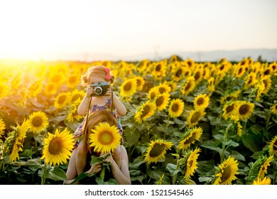A Sunflower Field, a Mother that holds in her Shoulders her Daughter. The Mother hide her Face with a Sunflower and the Little Girl hide hers with a Camera.