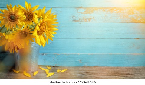Sunflower flowers in rustic vase on wooden table and rustic background