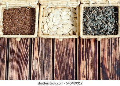 Sunflower, linseed and pumpkin seeds in bamboo baskets on a wooden board.