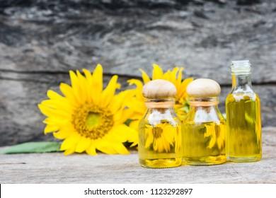 Sunflower oil in bottle glass on wood background.