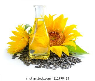 Sunflower oil is with the flowers of sunflower and grain on white background