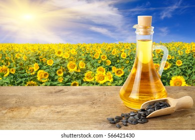 Sunflower oil in glass bottle and seeds on wooden table with field on the background. Photo with copy space area for a text