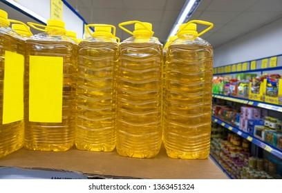 Sunflower oil plastic bottles on supermarket shelf. Financial management with economic foods background. Natural sunflower oils.