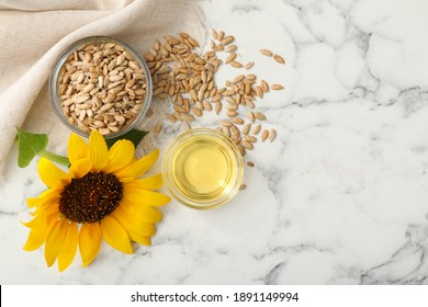 Sunflower, oil and seeds on white marble table, flat lay. Space for text