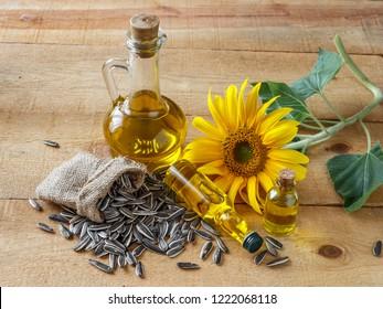 Sunflower oil, sunflower seeds on wooden surface