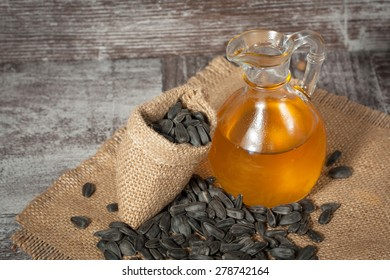 Sunflower oil and sunflower seeds in small sack on traditional rustic wooden background