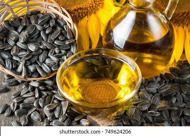 Sunflower oil and sunflower seeds in small sack on traditional rustic wooden background. Organic and eco food concept. Healthy food and fats.