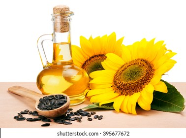 Sunflower oil, spoon with seeds and flowers lays on wooden table