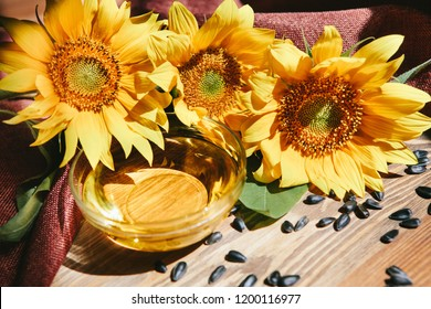 Sunflower oil with yellow flowers with black seeds on wooden background with sunshine