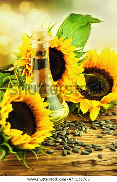 Sunflower seeds and bottle of oil on old wooden table.