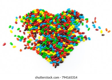 Sunflower seeds in multicolored chocolate coated on white background, design as heart shape style