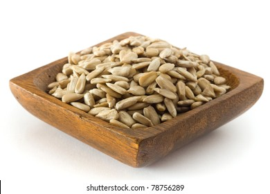 sunflower seeds in old wooden bowl against white background