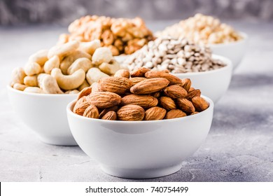 Sunflower seeds, pine nuts, cashew,walnut,almond in white bowls on concrete background. Selective focus,space for text.