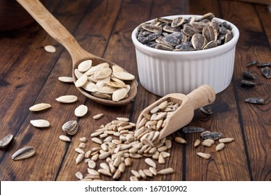 sunflower seeds and pumpkin seeds on wood background
