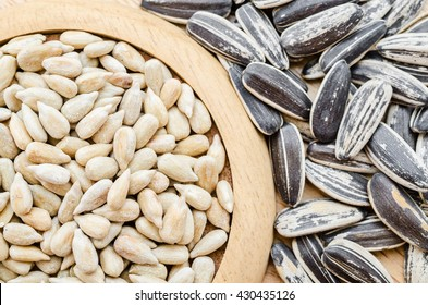 Sunflower seeds in wooden dish on wooden background.