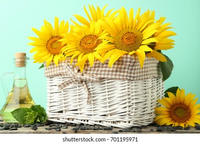 Sunflowers in basket with bottle of oil on wooden table