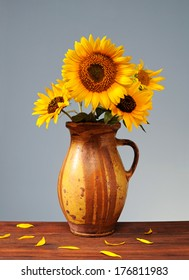 Sunflowers in ceramic vase on a wooden table