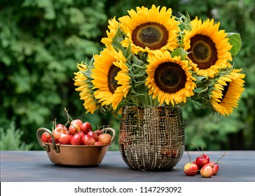 Sunflowers in a floral arrangement with cherries on a table show their Autumn colors or fall colours as table decoration with copy space