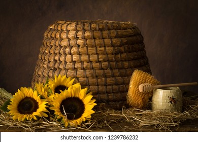Sunflowers with honeycomb and honey pot in front of an antique beehive