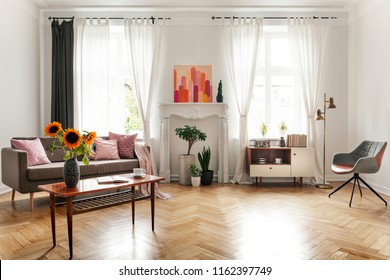 Sunflowers on wooden table next to sofa in spacious flat interior with armchair and poster. Real photo