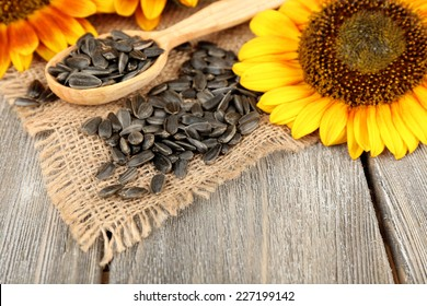 Sunflowers and seeds with spoon on wooden background