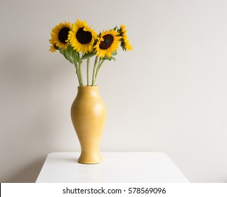 Sunflowers in tall yellow vase on white table against neutral background