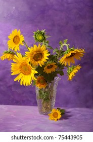 Sunflowers in a transparent glass vase on abstract background