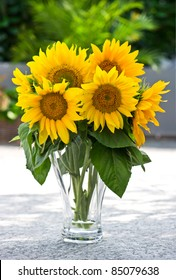 Sunflowers in a transparent glass vase on nature green background