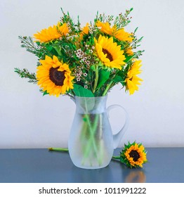 Sunflowers in a vase on a rustic, blue background